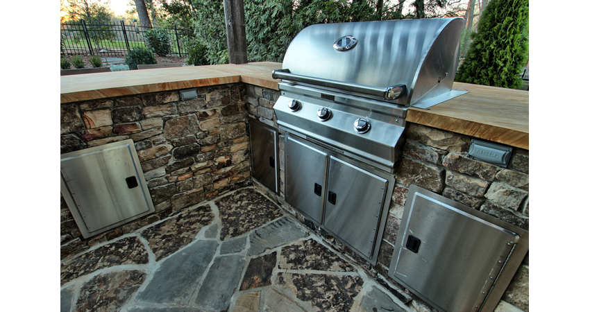 Outdoor kitchen with a grill built into a backyard design in Charlotte NC by Benton Outdoor Living