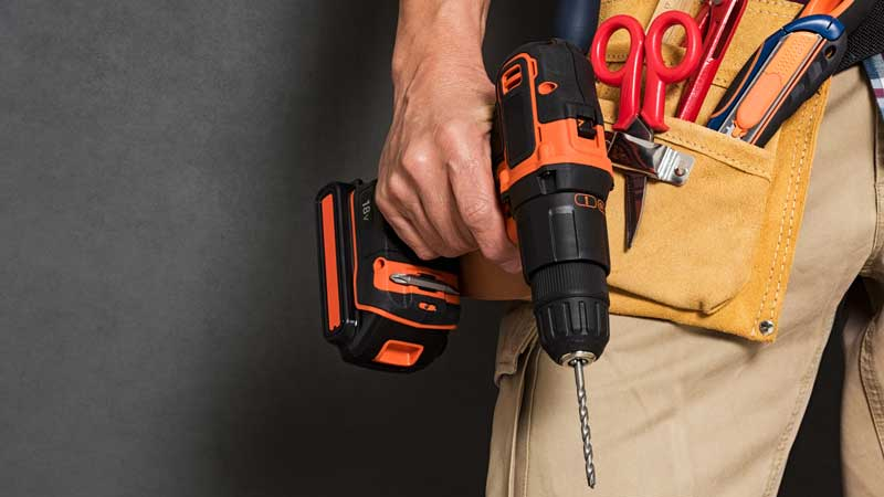 Handyman holding a drill with bit and toolbelt.