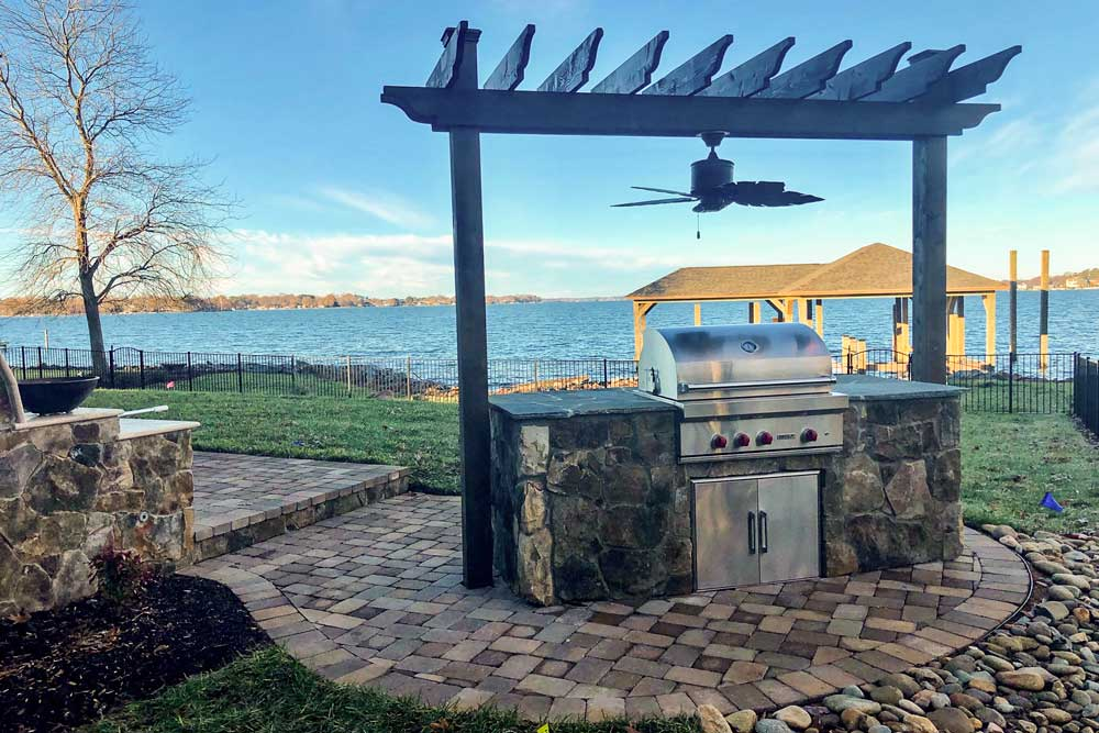 Rear yard of lakeside home in the Charlotte area with paver patio, grilling island with pergola and a view of the lake