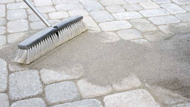 Brooming polymeric sand into pavers to help lock them together and form a bond much like one would do with grout for tiles.