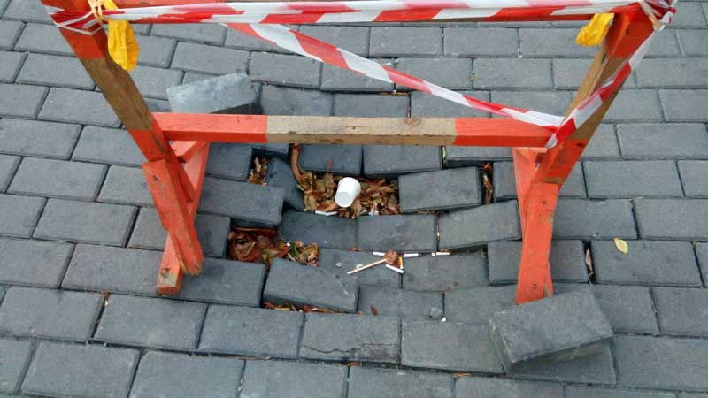 Wooden safety barrier on top of hole where concrete patio pavers have sunk into the ground and come apart.