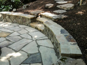 Patio with seat wall and stone steps that was created on a slope using cut and fill