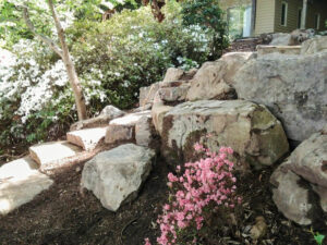 Natural looking rocky outcrop created at base of patio to prevent erosion on a sloped yard