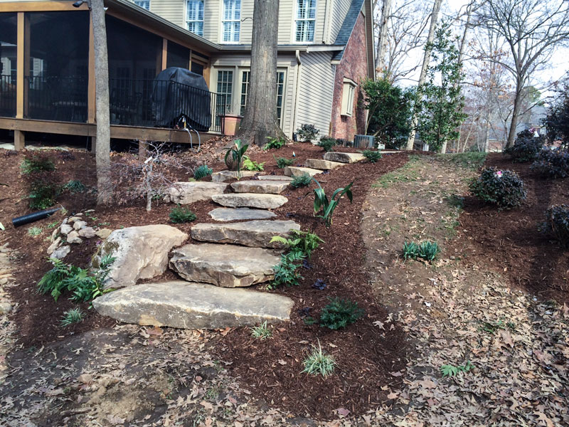Stone walking steps built into a sloped backyard to provide a walking path down to a flatter area