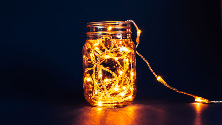 Mason jar with string of electric lights inside as an outdoor lighting idea for a table.
