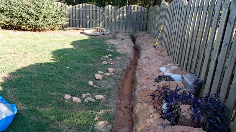 French drain trench in yard along fence for better drainage