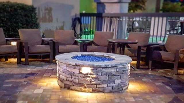 Gas fire pit with seats surrounding it near a pool