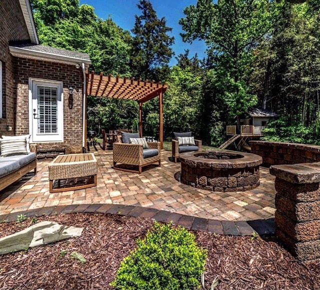 Charlotte backyard after a new paver patio with fire pit and seat wall plus landscaping by Benton Outdoor Living
