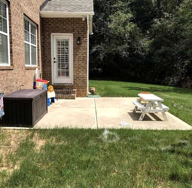 Before photo of a Charlotte backyard with a basic concrete patio.