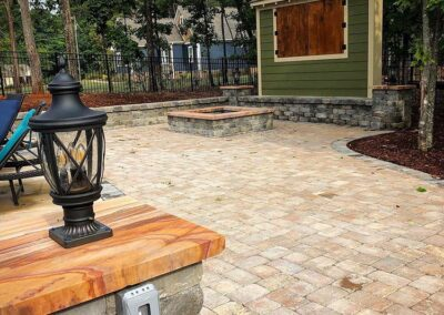 Fort Mill backyard with Paver Patio, fire pit and outdoor TV cabinet installed by Benton Outdoor Living