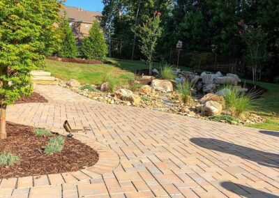 Backyard paver walkway, stairs and landscaping beds with rocks