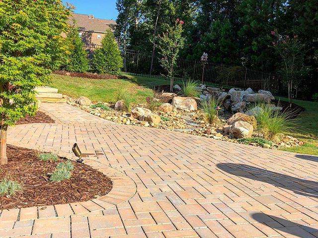 Backyard hardscape with paver walkway, stairs and landscaping beds with rocks