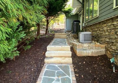 Stone walkway with paver surrounds and stone steps along the side of a house in Charlotte