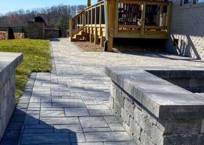Waxhaw, NC backyard with deck paver walkway, fire pit, grill area and seating walls.